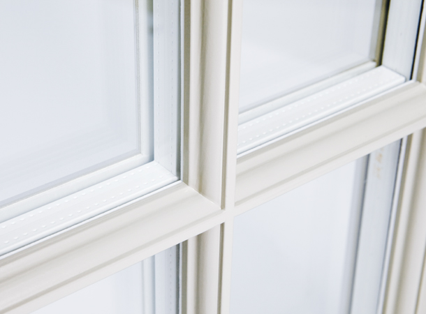 Refined slim timber glazing bars to a sliding sash window